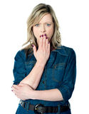 Pretty woman with hand over mouth Stock Photography