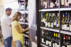 Pretty woman and handsome buying a wine bottle Stock Images