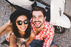 Pretty woman and handsome man posing near a vintage scooter Royalty Free Stock Image