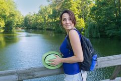 Pretty woman with a hat and a backpack on the bridge park Royalty Free Stock Photography