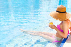 Pretty woman in a hat enjoying cocktail in a swimming pool Royalty Free Stock Photography