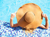 Woman in a hat enjoying a swimming pool Royalty Free Stock Photo