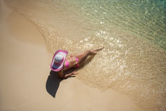 Pretty woman in the hat lying on the beach Stock Images