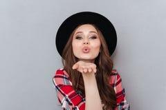 Pretty woman in hat and plaid shirt sending air kiss Stock Photos
