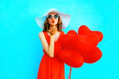 Pretty woman in hat sends an air kiss with balloons on blue ba. Pretty woman in hat sends an air kiss with a balloons on blue background Stock Photography