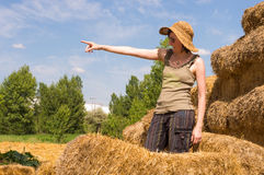 Pretty woman with hat standing in straw bales and pointing her finger toward the blue sky. Stock Photos