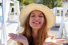 Pretty woman have fun on the beach. Close up portrait of a nice girl with closed eyes  and straw hat happy in her summer vacation royalty free stock photo
