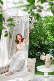 Pretty woman having fun in the summer garden gazebo. Opulent outdoor living area with flowers for celebration, tea party. Royalty Free Stock Image