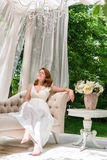 Pretty woman having fun in the summer garden gazebo. Opulent outdoor living area with flowers for celebration, tea party. Stock Image