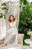 Pretty woman having fun in the summer garden gazebo. Opulent outdoor living area with flowers for celebration, tea party. Stock Photo
