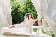 Pretty woman having fun in the summer garden gazebo. Opulent outdoor living area with flowers for celebration, tea party. Pretty woman having fun in the summer Royalty Free Stock Photos