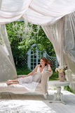 Pretty woman having fun in the summer garden gazebo. Opulent outdoor living area with flowers for celebration, tea party. Pretty woman having fun in the summer Stock Photo