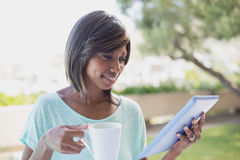 Pretty woman having her coffee outside using tablet pc Stock Photos
