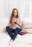 Pretty woman having a hot drink in the bed Stock Image