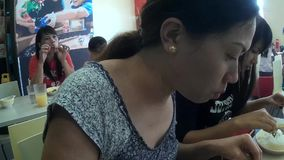 Pretty woman having mouthful eating big meal. San Pablo City, Laguna, Philippines - September 9, 2015: Ladies eating in a fast food restaurant stock video