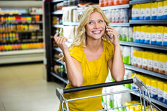 Pretty woman having phone call and pushing trolley Stock Photography