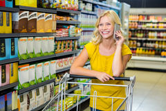 Pretty woman having phone call and pushing trolley Royalty Free Stock Image