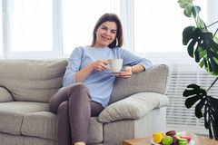 Pretty woman having rest on sofa with cup of coffee Royalty Free Stock Image