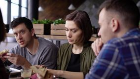 A pretty woman is having a sandwich with tuna, greens and tomatoes in a company of friends, discussing emotionally the. A beautiful adult woman eats at a stock video footage