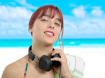 Pretty woman with headphones around the neck , on the beach Stock Photos