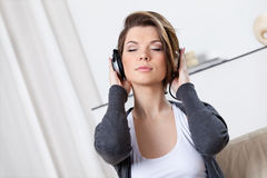 Pretty woman in headphones listens to music Stock Images