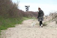 Pretty woman with her dog out in the park. Puppy white dog is running with it`s owner. royalty free stock photography