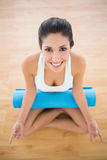 Pretty woman with her exercise mat sitting in lotus pose Royalty Free Stock Photo