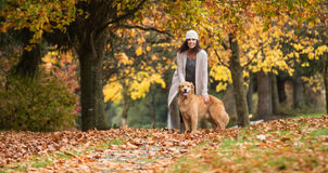 Pretty woman with her Golden Retriever Dog at a park in the Fall Royalty Free Stock Photography