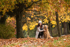 Pretty woman with her Golden Retriever Dog at a park in the Fall Royalty Free Stock Images