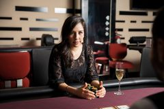 Pretty woman with her poker earnings. Portrait of a confident young woman holding her earnings after winning a poker game at a casino Stock Image