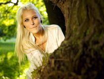 Pretty woman hiding behind tree. Pretty woman playing hide and seek in a park - hiding behind a tree Stock Photos