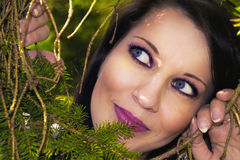 Pretty woman hiding behind the trees Stock Photo