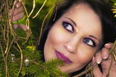 Pretty woman hiding behind the trees. Pretty tanned woman hiding behind the trees Stock Photo