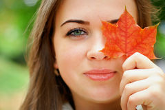 Pretty woman hiding eye behind the leaf Stock Photos