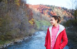 Woman hiker in bright red outdoor clothes is standing outdoors on the mountain river and forest backround. Pretty woman hiker in bright red outdoor clothes is stock photos