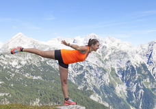 Pretty woman hiker standing on one leg with raised hands Stock Photo