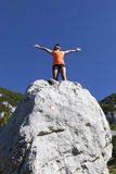 Pretty woman hiker standing on a rock with raised hands Royalty Free Stock Photography