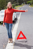 Pretty woman hitch hiking Stock Image