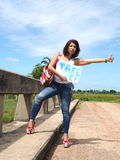 Pretty woman hitchhikes on a country road Royalty Free Stock Photo
