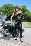 A pretty woman hold a black motorcycle helmet. And standing near by motorbike Stock Photography