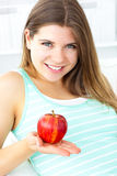 Pretty woman holding an apple sitting on a sofa Stock Image