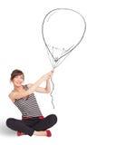 Pretty woman holding balloon drawing. Pretty young woman holding balloon drawing Stock Photo