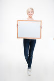 Pretty woman holding blank board. Full length portrait of a pretty woman holding blank board  on a white background Royalty Free Stock Photography