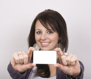 Pretty Woman Holding Blank Card. A pretty woman holds out a blank white card with both hands. Selective focus on her face Royalty Free Stock Photo