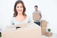 Pretty woman holding boxes in her new house Royalty Free Stock Image