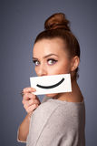 Pretty woman holding card with funny smiley on gradient background Stock Photography