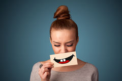 Pretty woman holding card with funny smiley on gradient background Stock Images