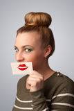 Pretty woman holding card with kiss lipstick mark on gradient background Stock Image
