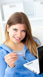 Pretty woman holding a card and a laptop. Portrait of a pretty woman holding a card and laptop looking at the camera at home Royalty Free Stock Image
