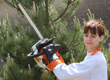 A pretty woman holding a chainsaw. A woman holding a chainsaw up ready to cut a pine-tree stock images